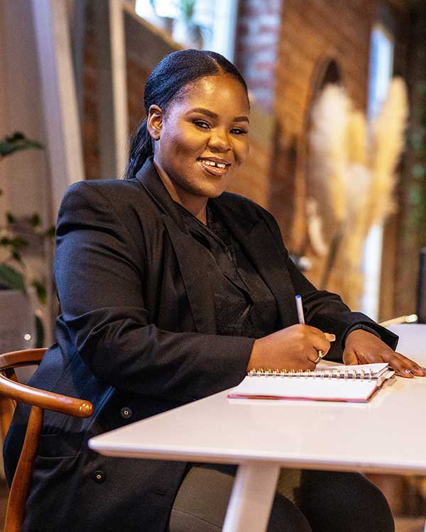 Zandile Chiwanza smiles as she writes in a notepad